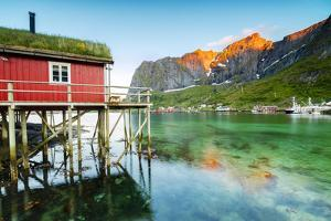Typical House of Fishermen Called Rorbu Lit Up by Midnight Sun, Reine, Nordland County by Roberto Moiola