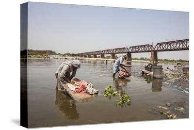 Women Wash Clothes in the Polluted Water of the Yamuna River