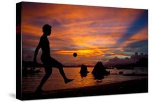 A Solomon Islander Kicks a Ball Against a Stunning Sunset Off Tetapare by Robin Moore
