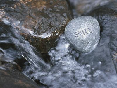 Rock with the Word Smile in Rushing Water--Photographic Print