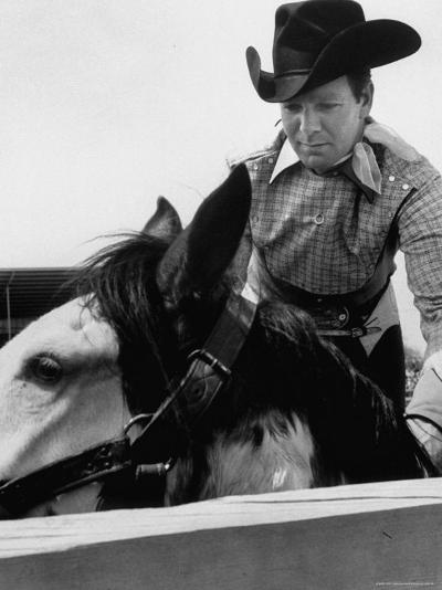 Rodeo Star Casey Tibbs Sitting in the Pen at a Rodeo Just Before His Horse Threw Him-Nat Farbman-Premium Photographic Print