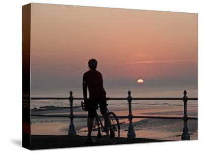 A Cyclist Pauses to Watch the Sunrise, on an Overlook Along the Ocean Front