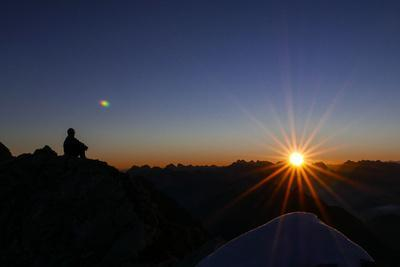 Mountaineer Admires Sunrise and Sunrays