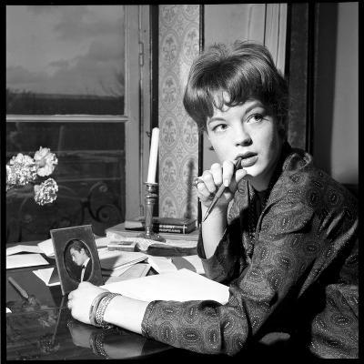Romy Schneider, Thougthful, Trying to Write a Letter in Front of Alain Delon's Picture-Marcel Begoin-Photographic Print