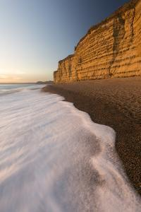 Foam on beach below cliffs at Burton Bradstock, Dorset, UK by Ross Hoddinott