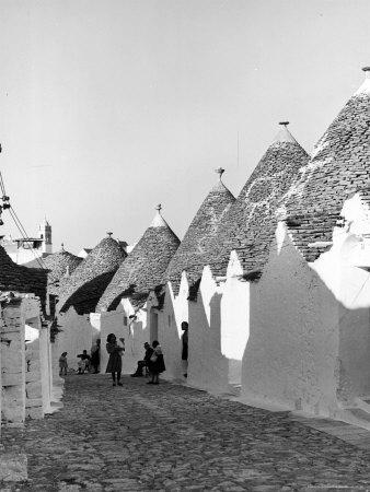 https://imgc.artprintimages.com/img/print/row-of-trulli-homes-made-from-limestone-boulders-and-feature-conical-or-domed-roofs_u-l-p4427c0.jpg?p=0