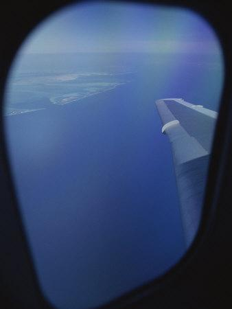 A View out of an Airplane Window over Water and Nearby Islands