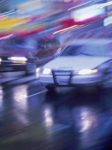 Police Car and Car on Wet Street, NYC by Rudi Von Briel