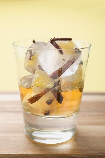 Rum and Ice Cubes with Spices and Pieces of Fruit in Glass-Foodcollection-Photographic Print