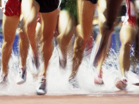 Runners Legs Splashing Through Water Jump of Track and Field Steeplechase Race, Sydney, Australia-Paul Sutton-Photographic Print