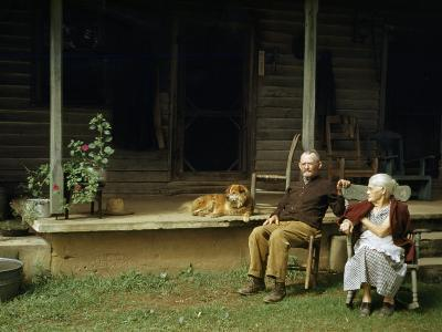 Rural Couple Sits in Chairs on Lawn, Dog Lies on Shady Porch Nearby--Photographic Print