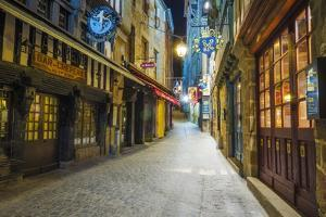 Shops and Cobblestone Street at Night, Mont Saint-Michel, Normandy, France by Russ Bishop