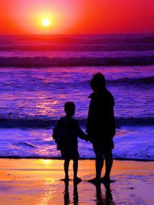 Sunset Silhouette of Mom and Boy Along Coast by Russell Burden