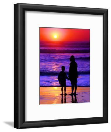 Sunset Silhouette of Mom and Boy Along Coast
