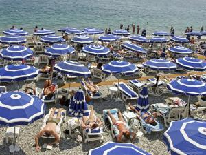 Blue Umbrellas and People Crowd Beach by Russell Mountford