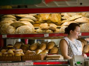 Woman in Bakery, Trogir, Croatia by Russell Young