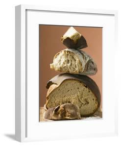 Rustic Bread, Two Loaves with Pieces Cut Off in a Pile