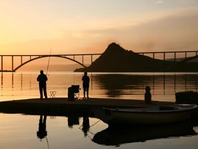 Couple Fishing from Stone Pier with Krk Bridge Joining Krk Island to Mainland