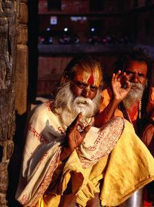 Portrait of Two Sadhus Making Hand Signals in Taumadhi Square, Bhaktapur, Nepal by Ryan Fox