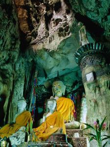 Seated Buddha Statues in Saffron Cloth Inside Cave, Chiang Dao, Thailand by Ryan Fox