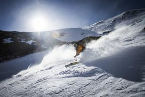 Male Skier Great Falls From The North Summit Snowfield At Big Sky Resort, Montana by Ryan Krueger