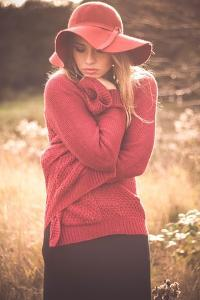 Young Woman Outdoors Wearing a Red Hat by Sabine Rosch