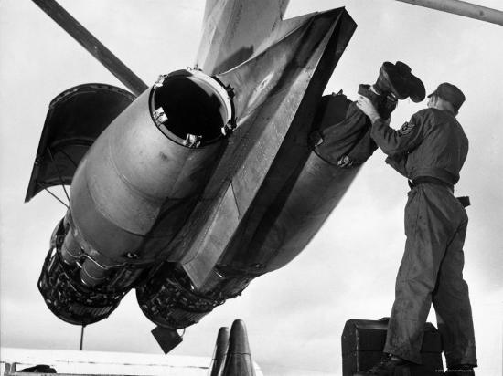 SAC's Maintenance Mechanic Sliding Into Barrel of Bomber's Jet Engine with the Help of His Partner-Margaret Bourke-White-Photographic Print