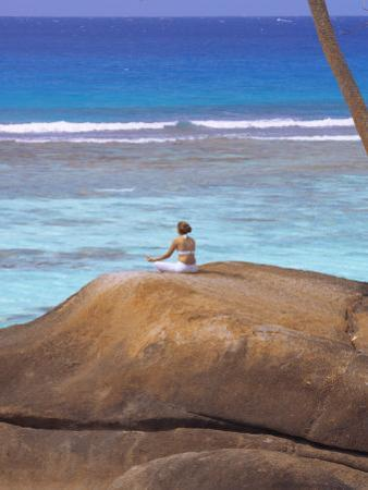 Young Woman Meditating on Rock, Seychelles, Indian Ocean, Africa by Sakis Papadopoulos