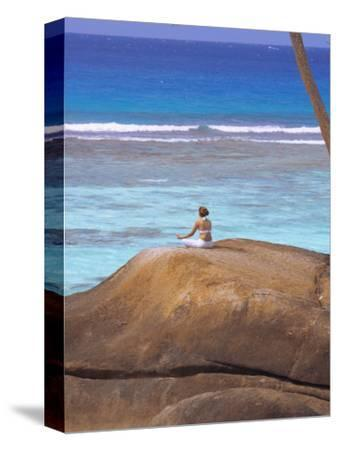 Young Woman Meditating on Rock, Seychelles, Indian Ocean, Africa