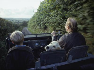 A Man and His Son and Dog Drive Down a Country Road Near their Home