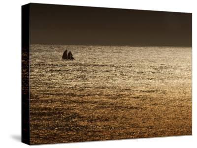 A Sailing Ship Crosses Waters Turned Gold by the Setting Sun