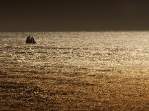 A Sailing Ship Crosses Waters Turned Gold by the Setting Sun by Sam Abell