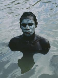Aboriginal Teen with a Mask of Mud, Swimming in a Billabong by Sam Abell