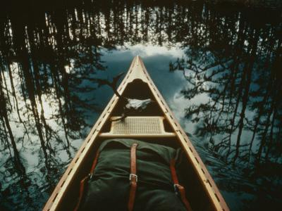 Bow of a Canoe Set against Trees Reflected in the Still Water
