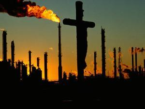 A Crucifix is Silhouetted against Refinery Stacks by Sam Kittner