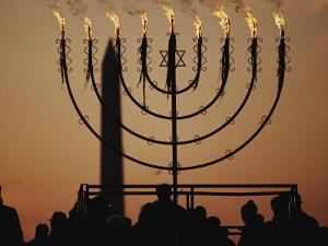 Silhouetted Worshippers Stand Before a Large Menorah Near the Washington Monument by Sam Kittner