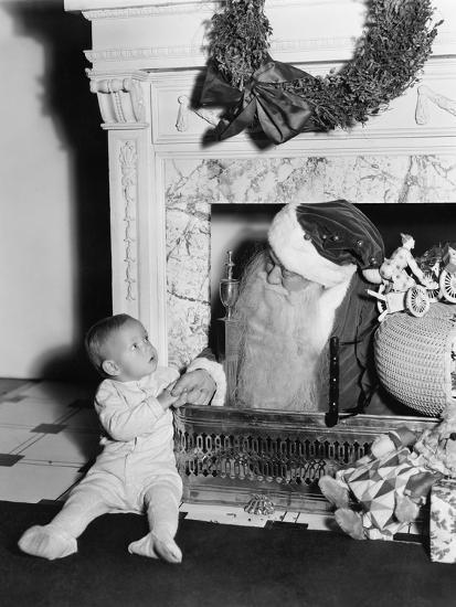 Santa Claus with a Little Boy in Front of a Fireplace--Photo
