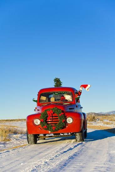 Santa Driving a Vintage Red Ford Pick-Up Truck Down a Snowcovered Rural Road-Design Pics Inc-Photographic Print