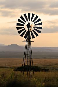 An Old Windmill on a Farm in a Rural or Rustic Setting at Sunset. by SAPhotog