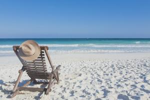 Beach Chair with a Hat, on an Empty Beach by Sasha Weleber