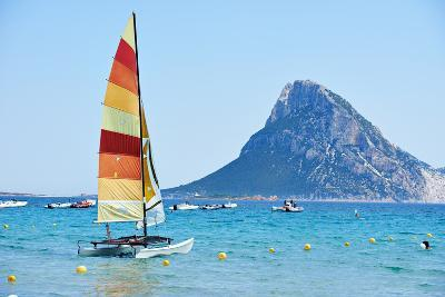 Scenic Italy Sardinia Beach Resort Landscape with Sail Boat and Mountains-kadmy-Photographic Print