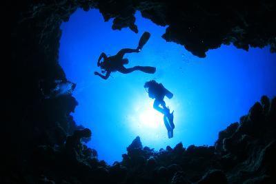 Scuba Divers Descend into an Underwater Cavern. Silhouettes against Sunburst-Rich Carey-Photographic Print