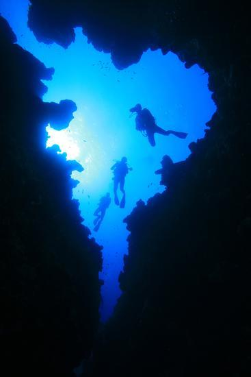 Scuba Divers Descend into Underwater Cavern, Silhouetted against Sun-Rich Carey-Photographic Print