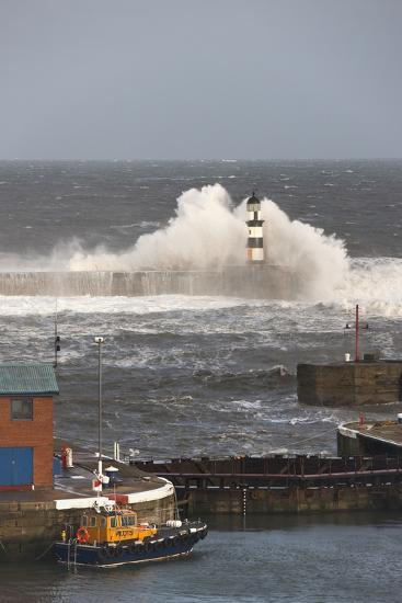 Seaham, Teesside, England; Waves Crashing into a Lighthouse and a Boat Along the Pier-Design Pics Inc-Photographic Print