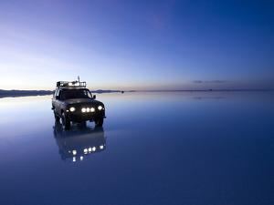 A 4X4 Rests in the Early Am Reflection in a Flooded Salt Flat In by Sergio Ballivian