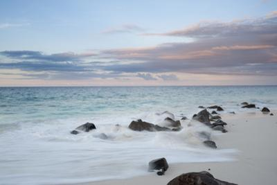 Long Exposure of Indian Ocean Surf Surging onto a Rocky Beach at Sunset by Sergio Pitamitz