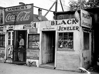 https://imgc.artprintimages.com/img/print/shack-like-black-jeweler-shop-next-to-food-store-covered-with-ads-in-a-slum-section-of-the-city_u-l-p43sam0.jpg?p=0