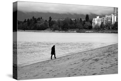 Figure Walking Alone Along Beach in Winter