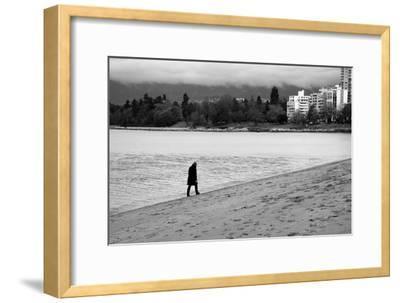 Figure Walking Alone Along Beach in Winter