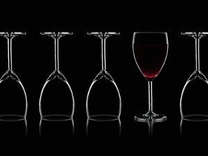 Row of Wine Glasses and a Glass of Red Wine Against a Black Background by Shawn Hempel